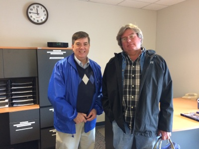 Two men - one in a blue jacket and one in a gray jacket - smile at the camera from Morehead State Public Radio studios.